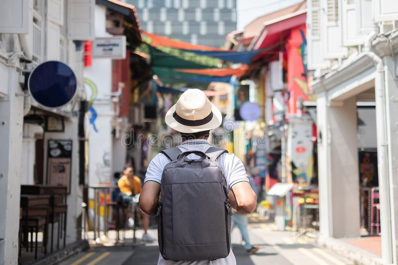 Hipster f?r ung man som reser med ryggs?cken och hatt, lycklig asiatisk handelsresande som g?r p? Haji Lane, och arabisk gata i S royaltyfria bilder