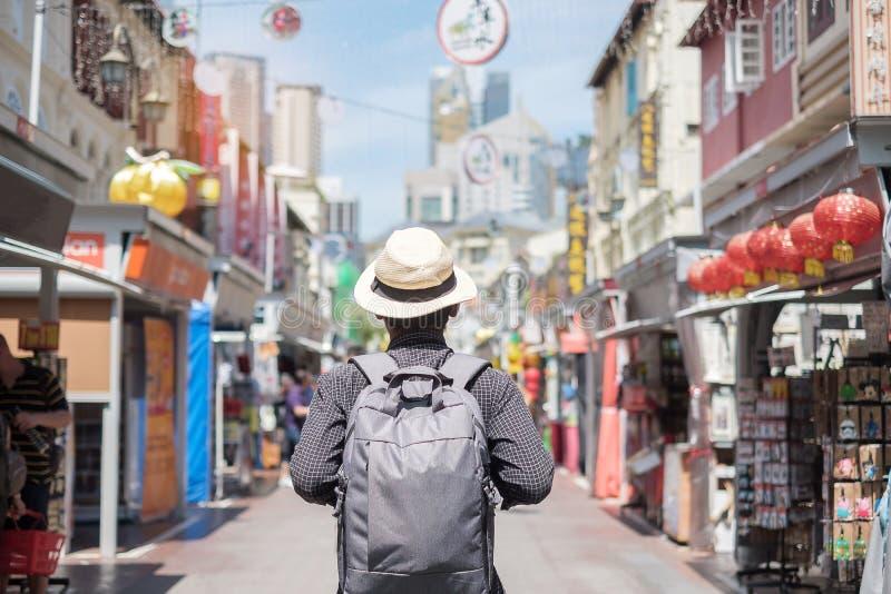 Hipster för ung man som solo reser med ryggsäcken och hatten, lycklig handelsresande som går på kineskvartergatamarknaden i Singa fotografering för bildbyråer
