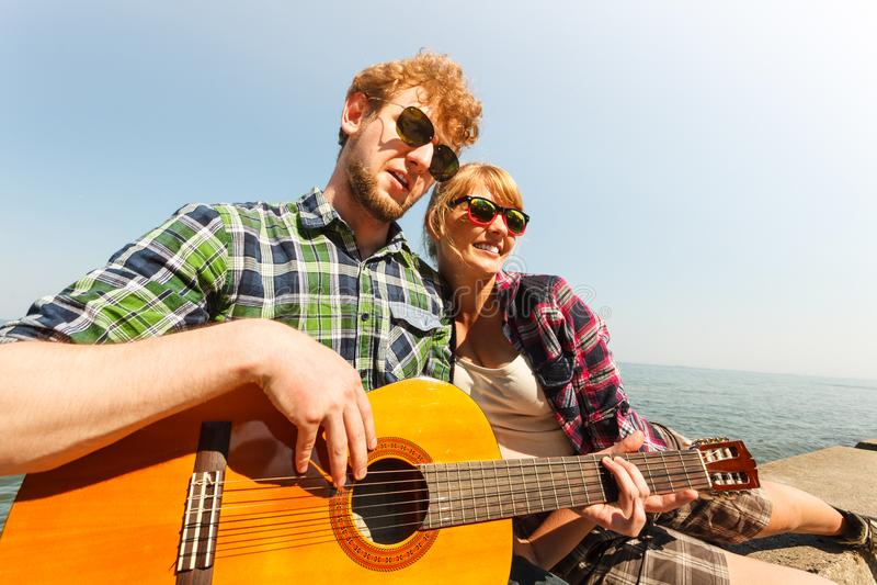 Hipster för ung man som spelar gitarren för kvinna fotografering för bildbyråer