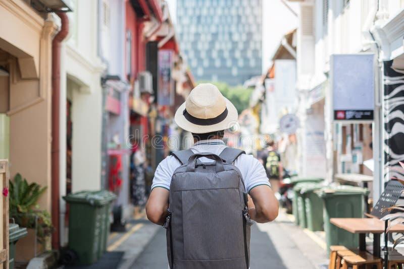 Hipster f?r ung man som reser med ryggs?cken och hatt, lycklig asiatisk handelsresande som g?r p? Haji Lane, och arabisk gata i S royaltyfri bild