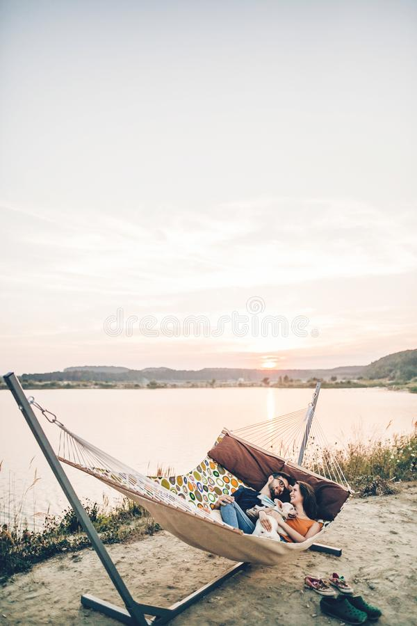 Hipster family on vacation concept, happy woman and man relaxing on a hammock at the beach with their cute bulldog pet, couple royalty free stock photo