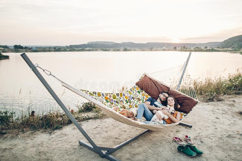 Hipster family on vacation concept, happy woman and man relaxing on a hammock at the beach with their cute bulldog pet, couple royalty free stock images