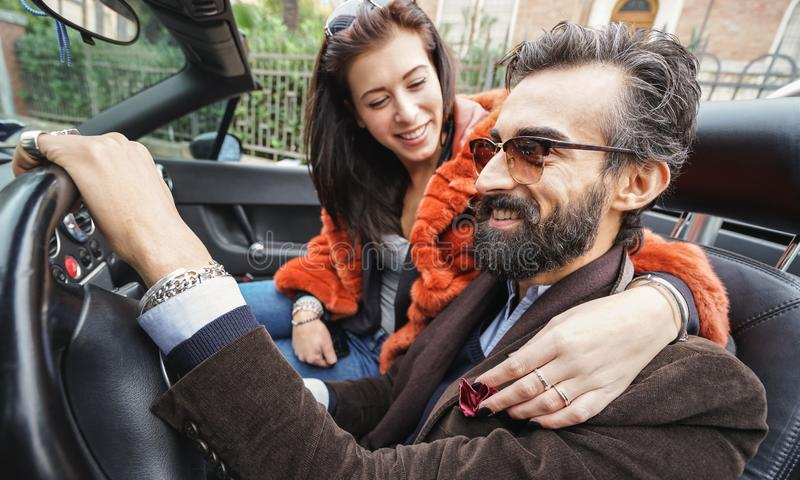 Hipster fashion couple ready for roadtrip on vintage sportscar transport - Travel lifestyle concept with happy people having fun royalty free stock photo