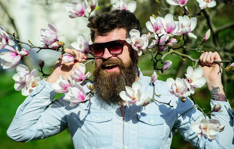 Hipster in fashionable sunglasses cheerfully posing with magnolia branches on background. Guy in modern stylish stock image