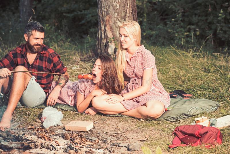 Hipster feed woman with roasted sausage. Bearded man relax with women at bonfire. Boyfriend and girlfriends camping in royalty free stock images