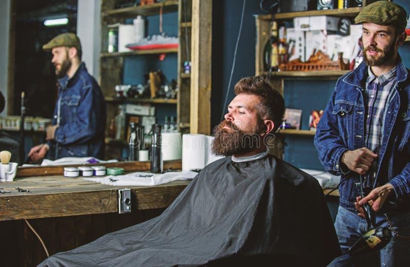 Hipster gebaard cliënt geworden kapsel De kapper met hairdryer blaast haar uit kaap weg Kapper met de hairdryerwerken  royalty-vrije stock fotografie