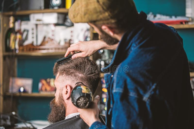 Hipster gebaarde cli?nt die kapsel krijgen Kapper met hairdryer het drogen en het stileren haar van cli?nt Kapper met hairdryer royalty-vrije stock foto's