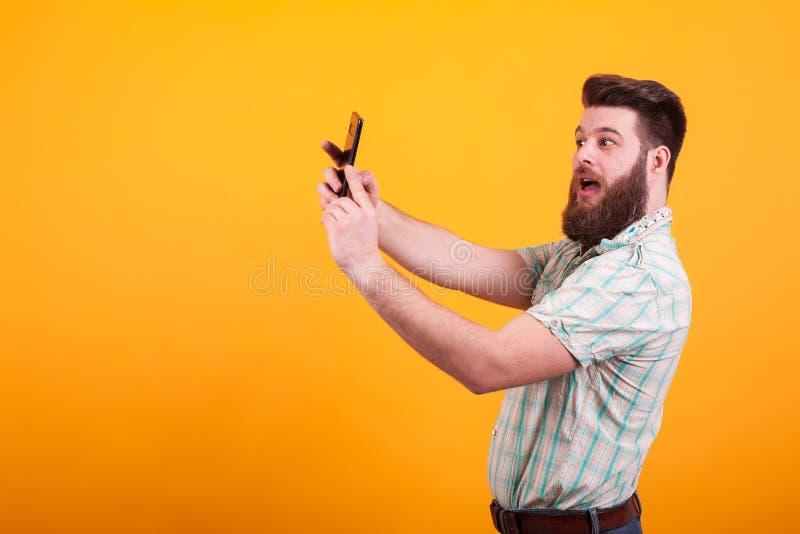 Hipster gebaarde mens die een selfie over gele achtergrond maken royalty-vrije stock fotografie