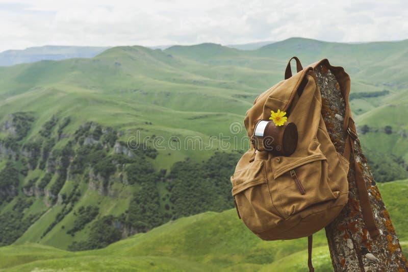 Hipster gele uitstekende rugzak met een mok vast op het met een vooraanzicht van het mokclose-up De zak van de reizigers` s reis  stock afbeeldingen