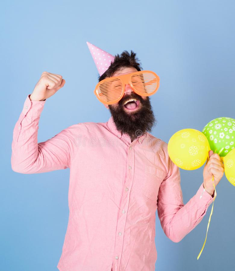Hipster in giant eyeglasses celebrates birthday. Guy in party hat with air balloons celebrates. Celebration concept. Man. With beard on cheerful face hold air stock photography