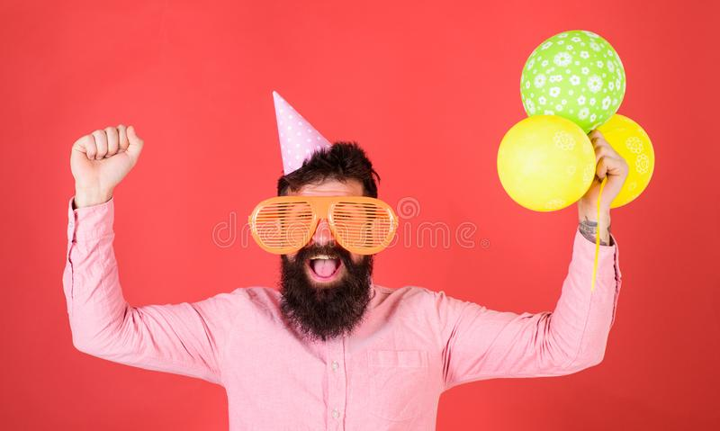Hipster in giant sunglasses celebrating birthday. Celebration concept. Guy in party hat celebrates holiday. Man with. Beard and mustache on happy face holds stock photo