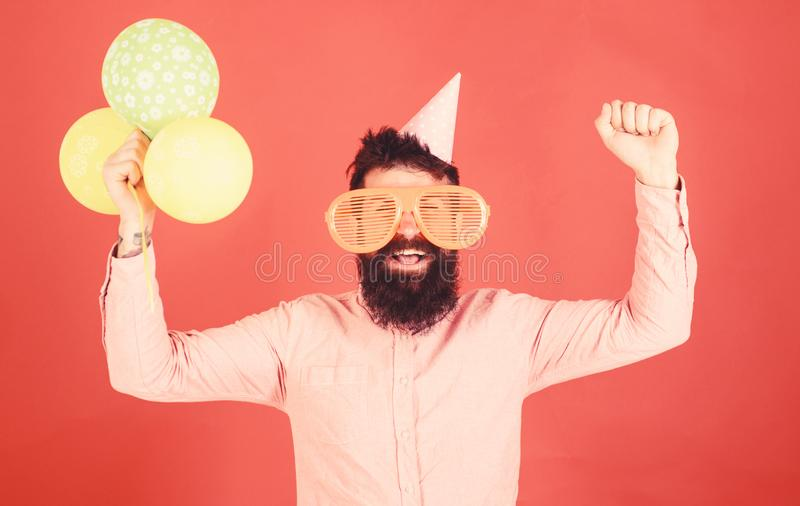 Hipster in giant sunglasses celebrating birthday. Guy in party hat celebrates holiday. Celebration concept. Man with. Beard and mustache on happy face holds stock photo