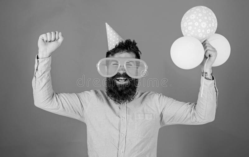 Hipster in giant sunglasses celebrating birthday. Guy in party hat celebrates holiday. Celebration concept. Man with. Beard and mustache on happy face holds stock images
