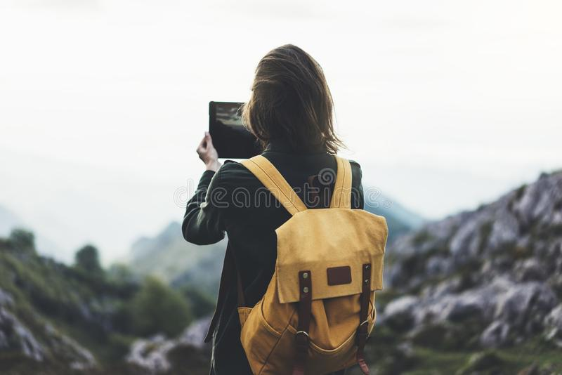 Hipster girl with backpack enjoying sunset on peak of foggy mountain, tourist traveler taking pictures of amazing landscape. On mobile sell phone digital camera stock photos