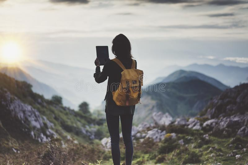 Hipster girl with backpack enjoying sunset on peak of foggy mountain, tourist traveler taking pictures of amazing landscape. On mobile sell phone digital camera stock photo