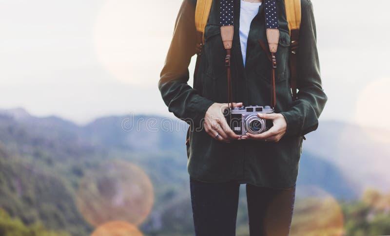 Hipster girl with backpack enjoying sunset on peak of foggy mountain, tourist traveler taking pictures of amazing landscape. On vintage photo digital camera on royalty free stock photos