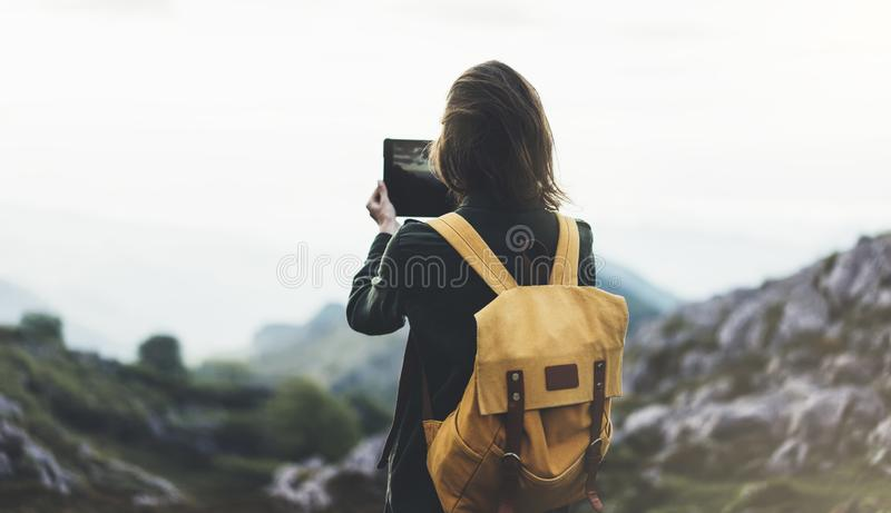 Hipster girl with backpack enjoying sunset on peak mountain, tourist traveler taking pictures landscape on mobile sell phone. Digital camera on background royalty free stock images
