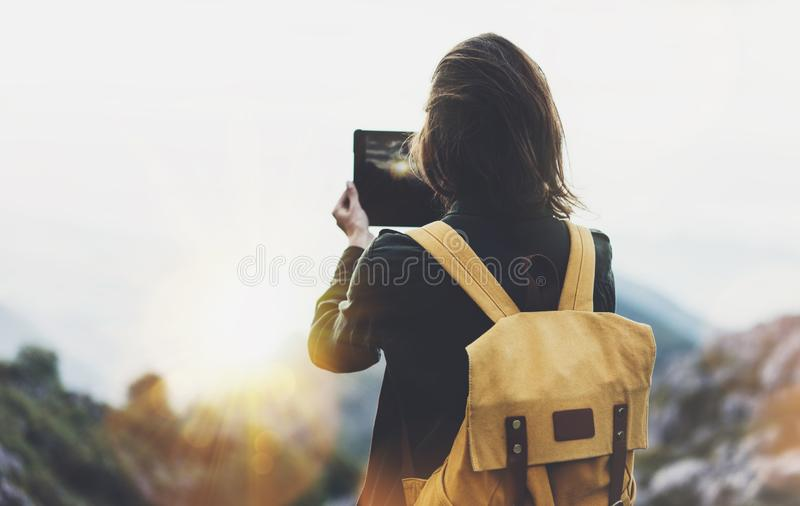 Hipster girl with backpack enjoying sunset on peak mountain, tourist traveler taking pictures landscape on mobile sell phone. Digital camera on background stock images
