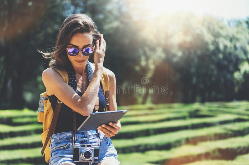 Hipster girl with backpack, sunglasses and vintage photo camera using tablet computer, copy space of blank empty mockup, view tour stock photos