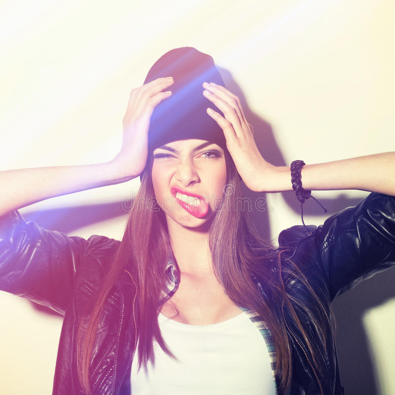 Hipster girl with beanie holding head making funny face. Closeup studio shot of pretty hipster teenage girl with beanie hat holding head making funny face royalty free stock photo