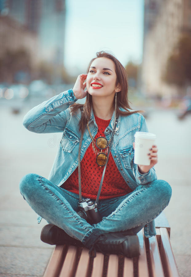 Hipster girl drinking coffee. Young beautiful hipster girl drinking coffee in the city stock image