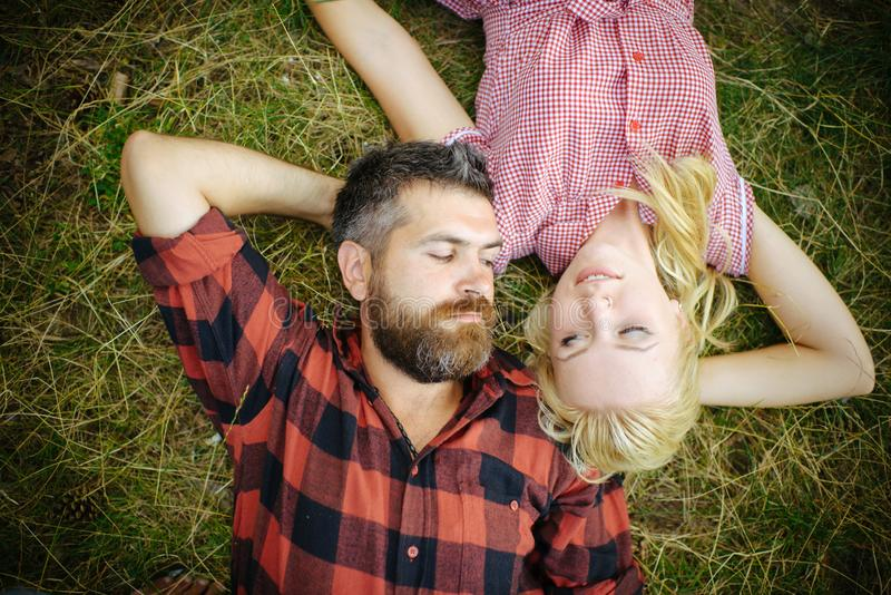 Hipster and girl enjoy summer day on nature. Couple in love relax on green grass. Bearded man and woman with long blond. Hipster and girl enjoy summer day on stock images