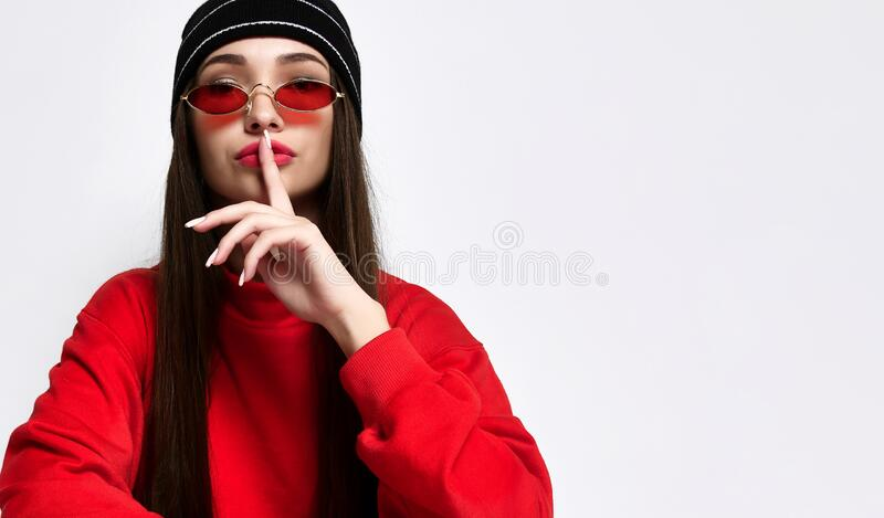 Hipster girl in a fashionable black hat headdress with long hair, showing hush, shhh, secrecy, silent sign, on light studio wall stock image