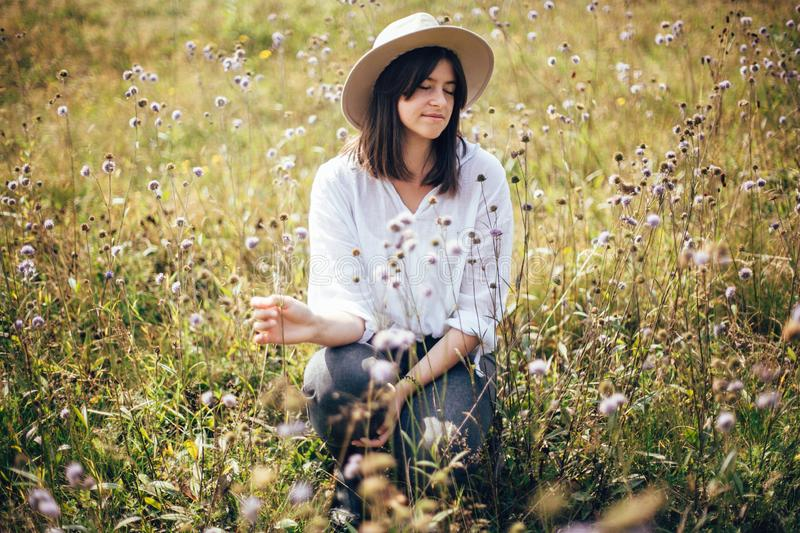 Hipster girl in hat traveling in sunny mountains, relaxing in wildflower meadow. Stylish happy woman enjoying hiking on top of royalty free stock photo