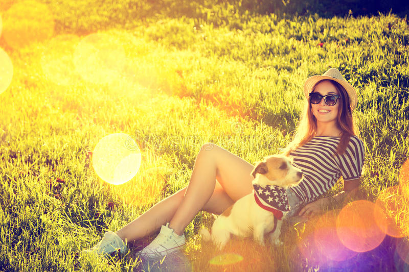 Hipster Girl with her Dog Lying on the Grass royalty free stock photo