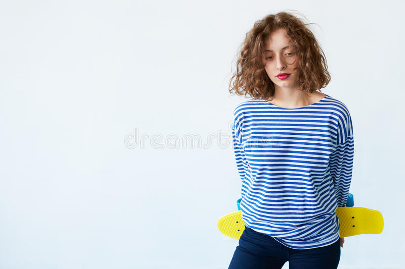 Hipster girl holding a skateboard isolated on white royalty free stock image