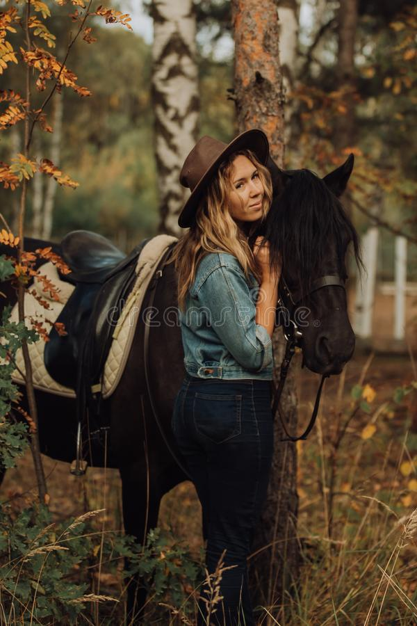 Hipster girl with a horse in the woods smiling royalty free stock images