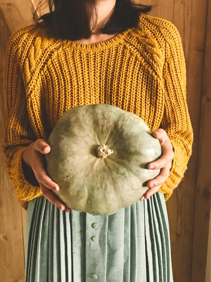 Free Hipster Girl In Yellow Sweater Holding Pumpkins On Rustic Wooden Background. Fall Rural Decor And Arrangement. Autumn Harvest. Royalty Free Stock Images - 161257689