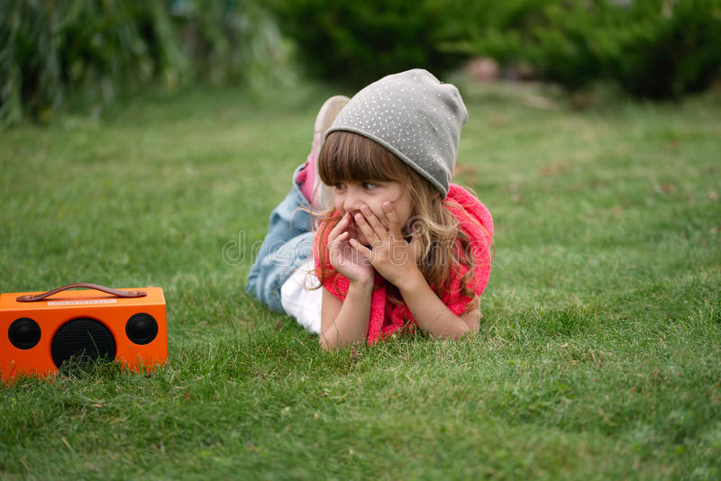 Hipster girl listens music on wireless retro looking speaker. Little beautiful hipster girl listens music on wireless retro looking speaker stock images
