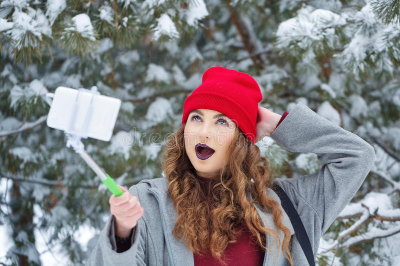 Hipster Girl makes selfie winter. Portrait of pretty attractive girl hipster winter park. She makes fun selfie on a smartphone. Youth street fashion. Winter fun stock images