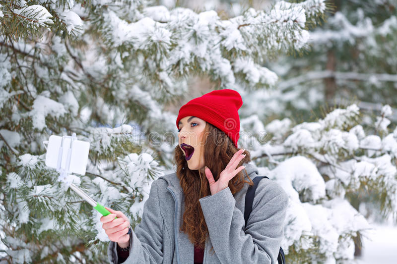 Hipster Girl makes selfie winter. Portrait of pretty attractive girl hipster winter park. She makes a funny selfie on a smartphone. Youth street fashion. Winter stock image