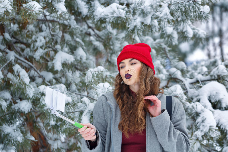 Hipster Girl makes selfie winter. Portrait of pretty attractive girl hipster winter park. She makes selfie smartphone on sending a kiss. Youth street fashion stock image