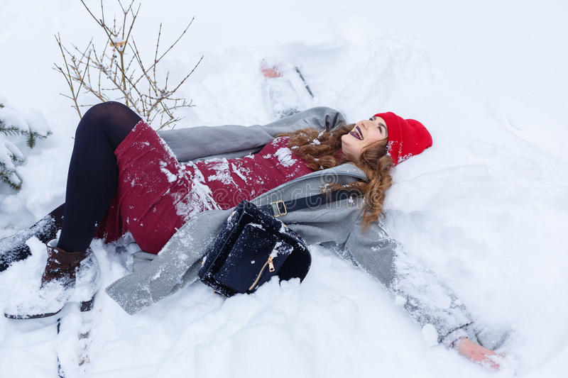 Hipster Girl making angel in snow stock photography