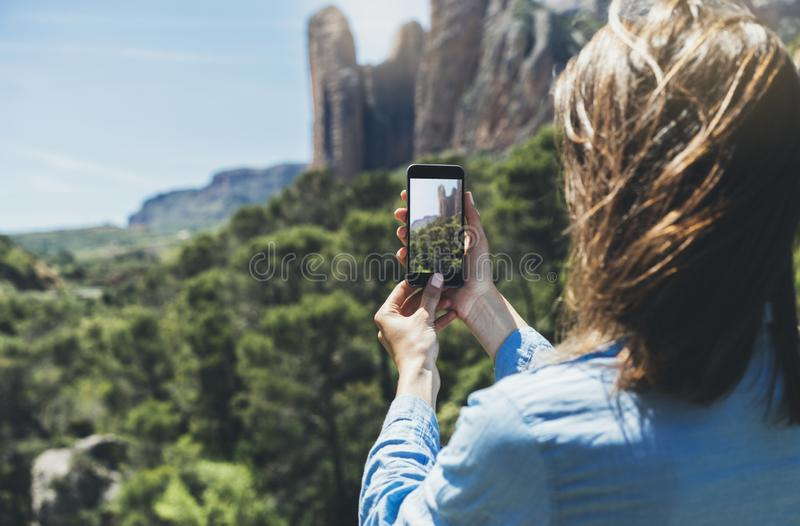 Hipster girl making photo on smartphone mobile closeup, view tourist hands using gadget phone in travel on background mountains. And sky landscape; finger touch royalty free stock photography