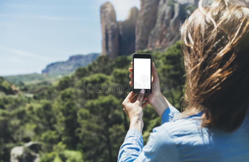 Hipster girl making photo on smartphone mobile closeup, view tourist hands using gadget phone in travel on background mountains. And sky landscape; finger touch royalty free stock photos
