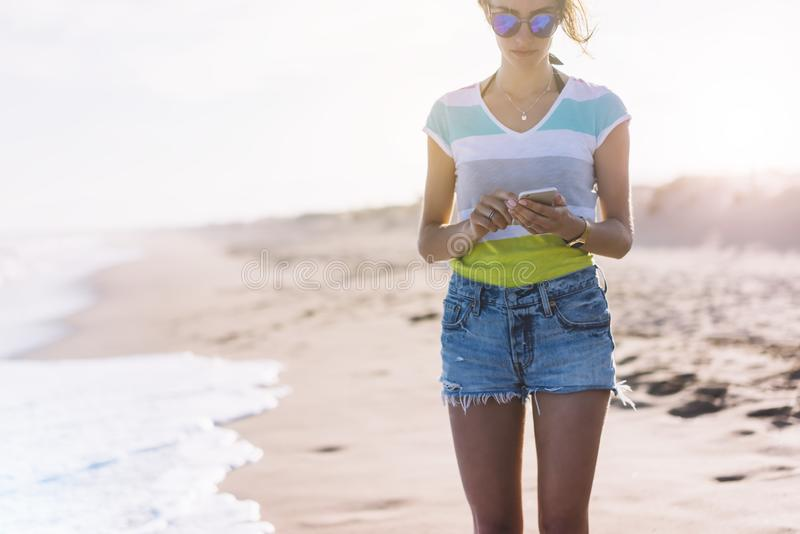 Hipster girl photograph on smart phone gadget in sand coastline beach, mock up of blank screen. Traveler hold and using in female stock images