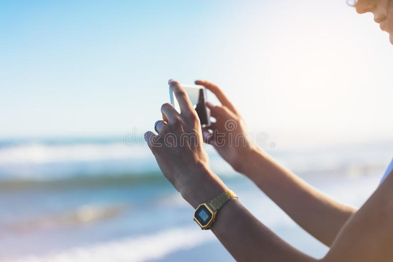 Hipster girl photograph on smart phone gadget in sand coastline, mock up of blank screen. Traveler hold and using in female hand royalty free stock photography