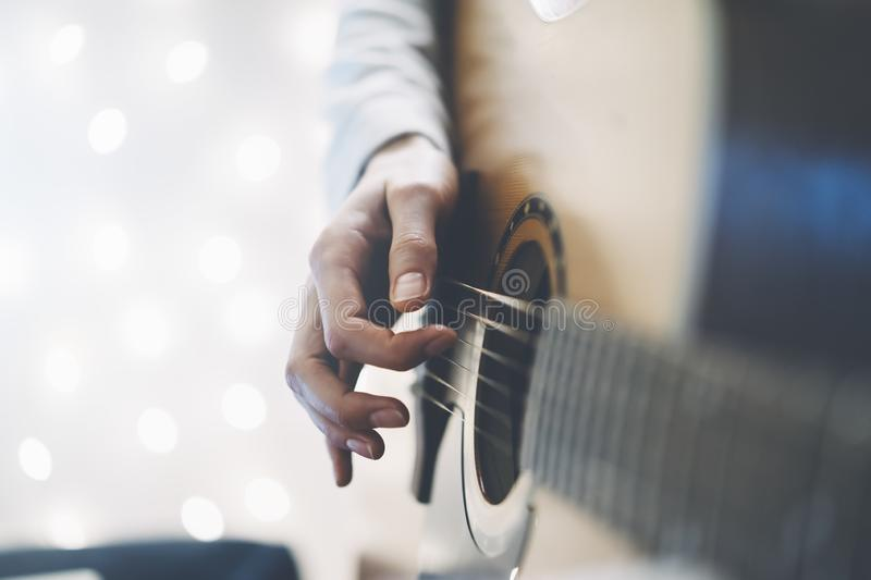 Hipster girl playing guitar in a home atmosphere, person studying on musical instrument on glow bokeh Christmas illimination, fema royalty free stock photos