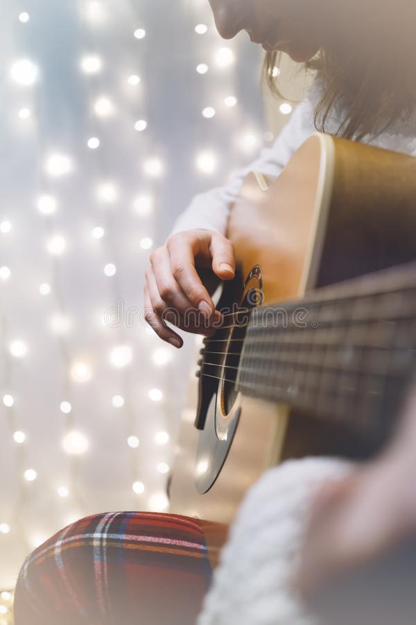 Hipster girl playing guitar in a homelike atmosphere, person studying on musical instrument on glow bokeh Christmas illimination stock photography