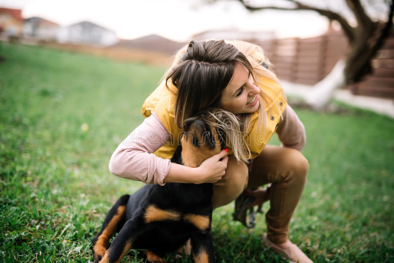 Hipster girl playing and hugging a rottweiler puppy. Woman playing fetch with ball and dog stock images