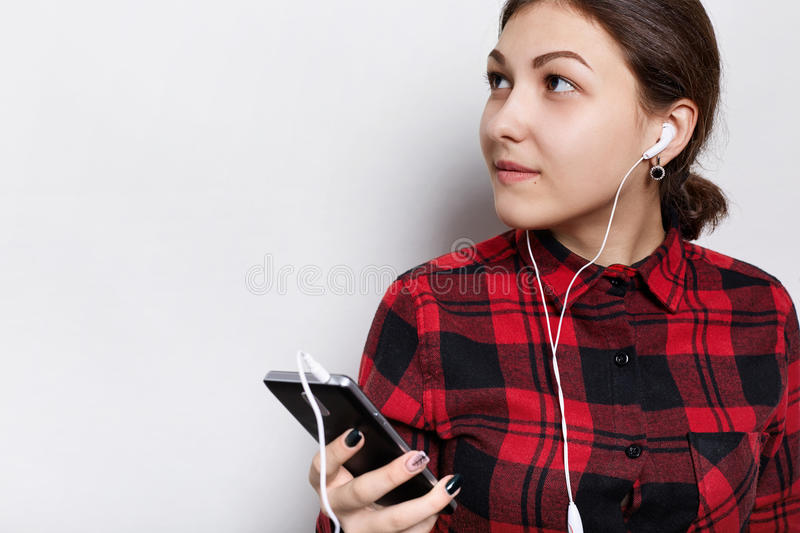 Hipster girl in red checked shirt having hair braided in a tail holding cell-phone listening to music or audiobook with headphones royalty free stock images