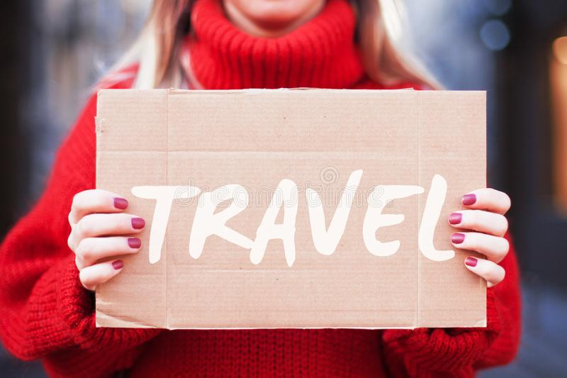A hipster girl in a red sweater holds a cardboard tablet with the inscription `travel. stock images