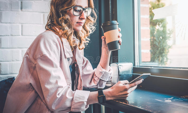 Hipster girl sitting in cafe at black table, drinking coffee and using smartphone. Businesswoman working online. stock photos