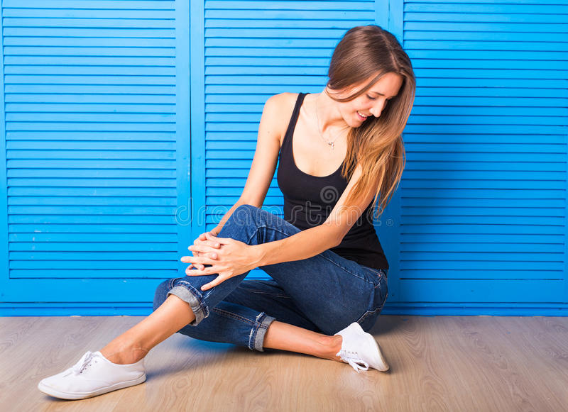 Hipster girl sitting on the floor against blue background. royalty free stock images