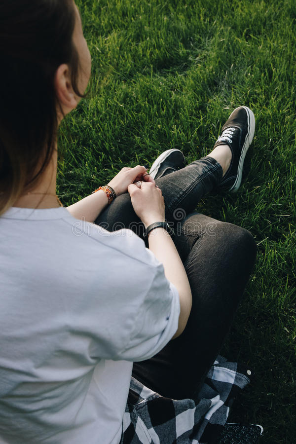 Hipster girl sitting on the grass stock photos