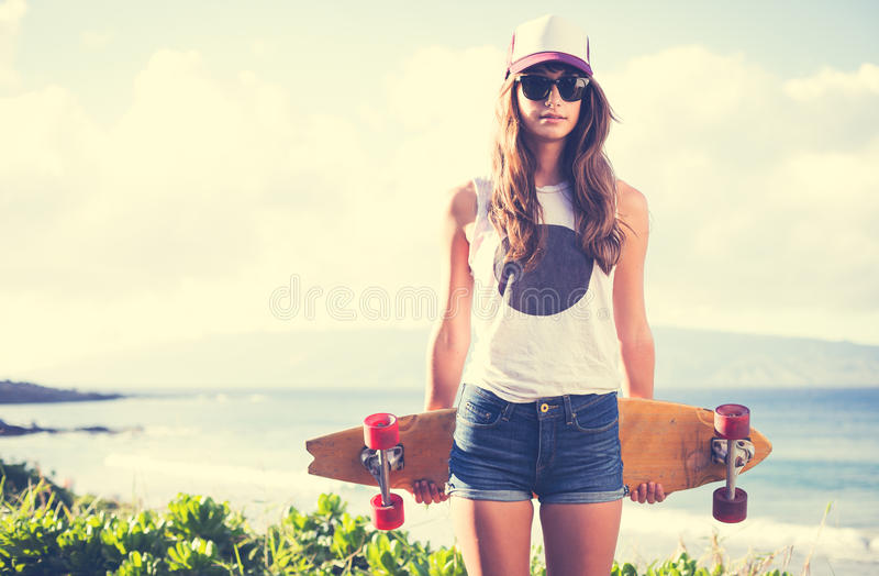 Hipster girl with skate board wearing sunglasses stock images